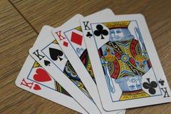 Cartes de tisonnier sur un backround en bois, l'ensemble de rois de trèfle, les diamants, les pelles, et les coeurs Images libres de droits