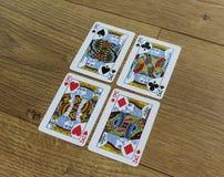 Cartes de tisonnier sur un backround en bois, l'ensemble de rois de trèfle, les diamants, les pelles, et les coeurs Photo stock