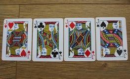 Cartes de tisonnier sur un backround en bois, l'ensemble de valets de trèfle, les diamants, les pelles, et les coeurs Images libres de droits