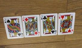 Cartes de tisonnier sur un backround en bois, l'ensemble de valets de trèfle, les diamants, les pelles, et les coeurs Images stock