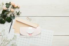 Cartes et enveloppes d'invitation de mariage sur la table en bois blanche, à photos libres de droits