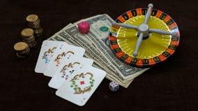 Cartes et roulette d'argent sur un fond foncé Photographie stock