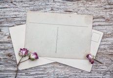 Cartes postales de vintage et roses de thé sèches sur le vieux bois Images stock