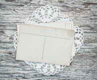 Cartes postales de vintage sur la dentelle et le vieux bois Images stock