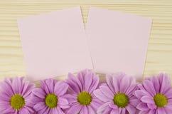 Cartes roses vierges et fleurs roses sur le fond en bois Image libre de droits