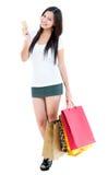 Cartão de crédito da terra arrendada da mulher nova e sacos de compra Foto de Stock