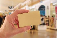 Cartão de crédito do ouro da terra arrendada da mão na alameda de compra Fotos de Stock Royalty Free