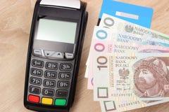 Cartão polonês do dinheiro e de crédito da moeda com terminal do pagamento no fundo, conceito da finança Fotografia de Stock Royalty Free