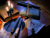 Cartographer's desk. Desk of a cartographer of the past, with antique maps, and a compass,  illuminated by candles on a candelabra Stock Photo