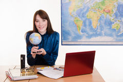 Cartographer sitting at the table with a globe in her hands Stock Photo