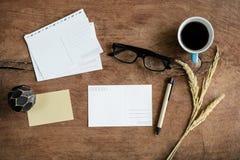 Cartolina in bianco con caffè sulla tavola di legno fotografia stock