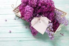 Cartolina con i fiori lilla sul vassoio e sul cuore decorativo Fotografia Stock Libera da Diritti