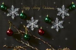 Cartolina con le palle rosse e verdi luminose con i fiocchi di neve Immagini Stock Libere da Diritti