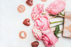 Cartolina d'auguri amorosa con le rose rosa, il cioccolato con il simbolo del cuore ed il testo con amore su fondo di legno bianc Fotografie Stock
