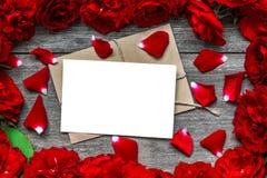 Cartolina d'auguri in bianco nel telaio fatto dei fiori e dei petali delle rose rosse Fotografie Stock Libere da Diritti