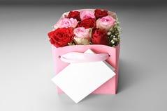 Cartolina d'auguri in bianco sopra la scatola delle rose Immagine Stock