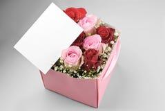Cartolina d'auguri in bianco sopra la scatola delle rose Immagini Stock