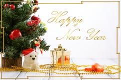 Cartolina d'auguri con l'albero di Natale, il contenitore di regalo dell'oro, le palle, l'orso del giocattolo, le caramelle e le  Fotografia Stock Libera da Diritti
