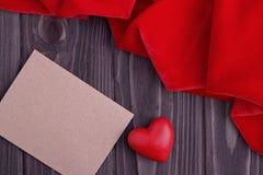 Cartolina d'auguri con un cuore rosso e spazio per testo su un fondo di legno marrone Immagine Stock