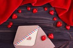 Cartolina d'auguri con un cuore rosso e spazio per testo su un fondo di legno marrone Immagini Stock