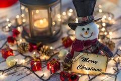 Cartolina d'auguri della tenuta del pupazzo di neve per il nuovo anno o il natale con gli ornamenti di natale fotografie stock libere da diritti
