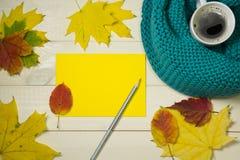 Cartolina d'auguri di autunno Umore di autunno con il concetto del caffè Pagina le foglie di autunno con la busta di yello su fon fotografia stock