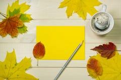 Cartolina d'auguri di autunno Umore di autunno con il concetto del caffè Pagina le foglie di autunno con la busta di yello su fon immagine stock