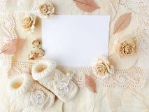 Cartolina d'auguri di battesimo o neonata Carta in bianco con le scarpe della neonata sul fondo del biege Disposizione piana Vist Immagine Stock