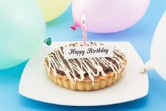 Cartolina d'auguri di buon compleanno con la crostata, la candela ed i palloni Fotografie Stock