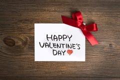 Cartolina d'auguri di giorno di biglietti di S. Valentino e piccolo regalo, decorazione del cuore sopra fondo di legno Saluti del Fotografie Stock