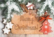 Cartolina d'auguri di Natale con i ramoscelli sotto neve, i giocattoli ed i biscotti Fotografia Stock Libera da Diritti