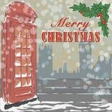 Cartolina d'auguri di Natale con la cabina telefonica rossa famosa di Londra ed il ramo santo Fotografie Stock Libere da Diritti