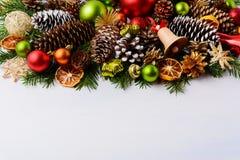 Cartolina d'auguri di Natale con le pigne e la campana di tintinnio di legno Fotografie Stock