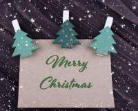 Cartolina d'auguri di natale di Natale con l'albero di Natale sulle mollette da bucato su fondo di legno scuro Fotografie Stock
