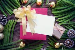 Cartolina d'auguri di Natale e contenitore di regalo di Natale sul fondo di legno della tavola Priorità bassa di Buon Natale e di immagini stock libere da diritti