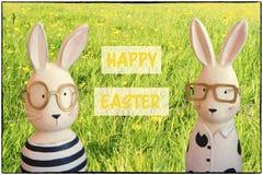Cartolina d'auguri di Pasqua con i coniglietti nel prato di primavera fotografie stock