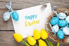 Cartolina d'auguri di Pasqua con le uova blu e bianche ed i tulipani gialli Fotografie Stock Libere da Diritti