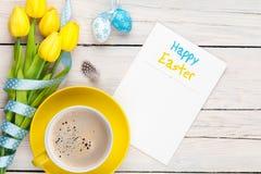 Cartolina d'auguri di Pasqua con le uova blu e bianche, tulipani gialli e Fotografia Stock