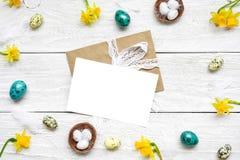 Cartolina d'auguri di Pasqua nel telaio fatto delle uova di quaglia, dei fiori della molla e delle piume Compisition di Pasqua immagini stock