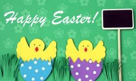 Cartolina d'auguri fatta a mano di Pasqua: pollo covato in guscio d'uovo con la lavagna isolata sul fondo del fiore Immagine Stock
