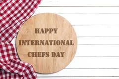 Cartolina d'auguri internazionale di giorno del cuoco unico Tagliere con il tovagliolo immagini stock libere da diritti