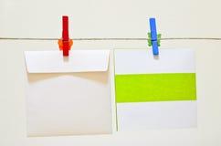 Cartolina d'auguri rossa e blu della holding del clothes-pin Fotografia Stock Libera da Diritti