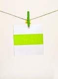 Cartolina d'auguri verde della holding del clothes-pin Fotografia Stock Libera da Diritti