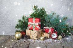 Cartolina di Natale, candele, orologio, fondo di legno, rami di albero, bastoncini di zucchero, notte di San Silvestro immagini stock