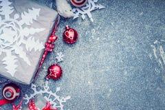 Cartolina di Natale con i fiocchi di neve della carta fatta a mano, i contenitori di regalo e le decorazioni rosse su fondo rusti Immagini Stock