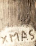 Cartolina di Natale con il natale dell'iscrizione nella neve su un fondo di legno Fotografie Stock