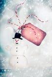 Cartolina di Natale con il pupazzo di neve fatto a mano ed etichetta sul fondo del bokeh di inverno Fotografia Stock