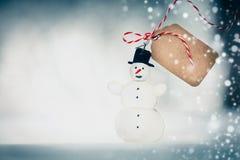 Cartolina di Natale con il pupazzo di neve fatto a mano, l'etichetta e la neve sul fondo del bokeh di inverno Immagine Stock