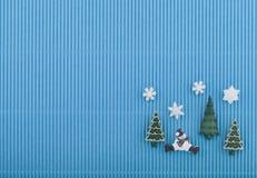 Cartolina di Natale con il pupazzo di neve, gli alberi ed i fiocchi di neve su carta ondulata blu Fotografia Stock Libera da Diritti