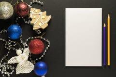 Cartolina di Natale con la decorazione, le matite e uno strato di Libro Bianco immagini stock libere da diritti